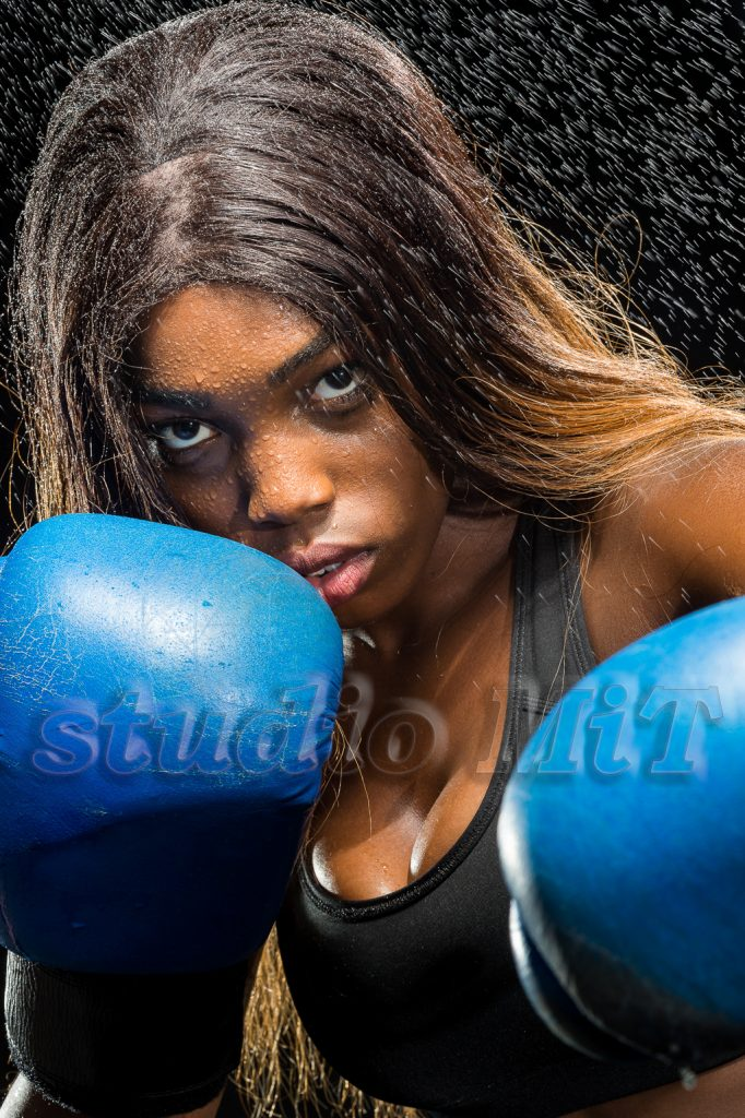 Portrait of female boxer with gloves against black background